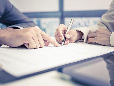 una mano che indica un foglio e un'altra che scrive