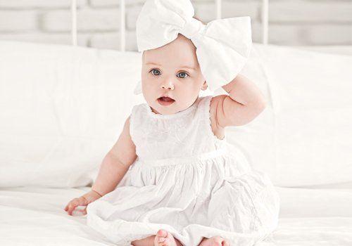 bambina con abito bianco e fiocco in testa