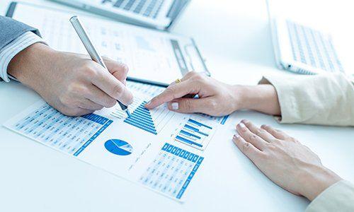 una mano che indica un foglio con un grafico e un'altra con una penna in mano