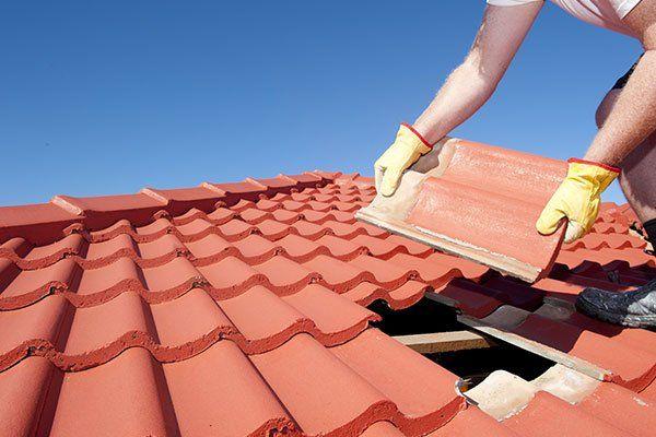 due mani di un muratore che posizionano una tegola su un tetto