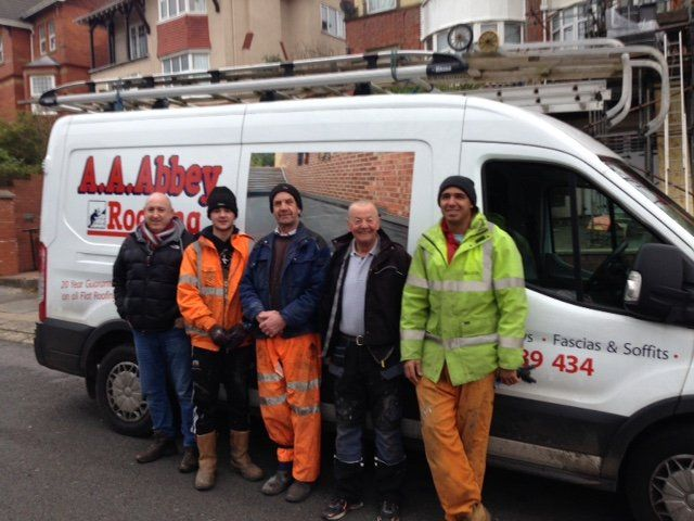 qualified roofers standing in front of their vehicle
