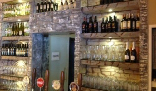 Parete di pietra del bar con gli scaffali pieni di bottiglie di vino,coppe e bicchieri