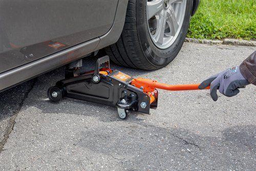 meccanico mentre solleva un'auto con un crick