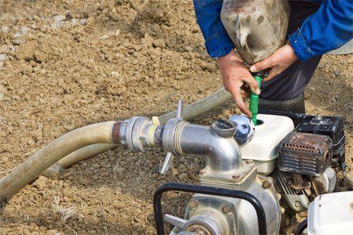 L'immagine ritrae un operaio che si occupa di riparare  pompe idriche