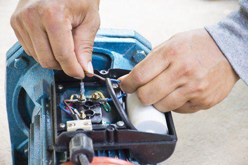 l'immagine ritrae una mano che ripara un impianto