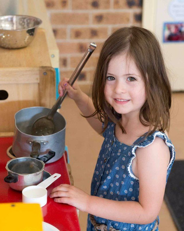 A little girl pretending to cook at our day care centre in St. Clair