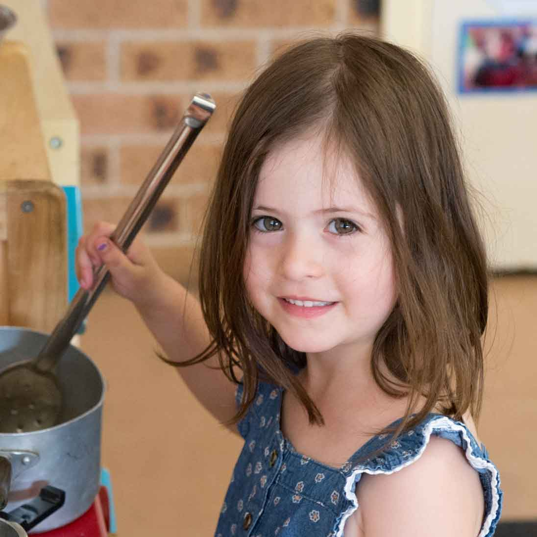 little girl playing with kitchen toys