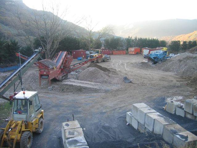 scavatrice di color arancione al lavoro, si vede una montagna di terra