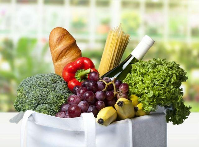 una borsa della spesa con delle verdure, pasta e vino