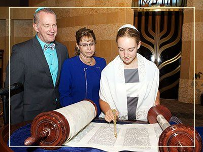 A Jewish Girl in the temple for her Bat Mitzvah. She is holding a yad in front of the Torah