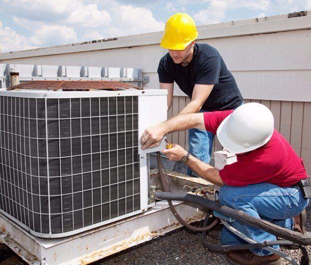 HVAC technicians repairing a compressor in Spring, TX