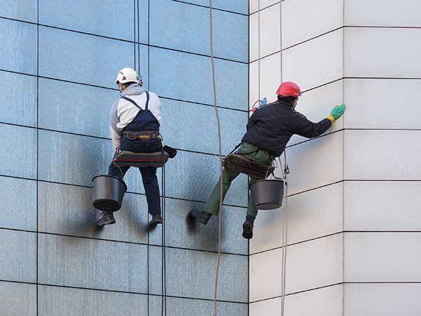due operai puliscono le finestre di un grattacielo