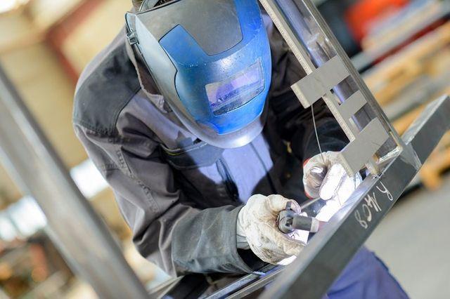 lavoratore con gli elementi di saldatura maschera protettiva in strutture produzione laboratorio