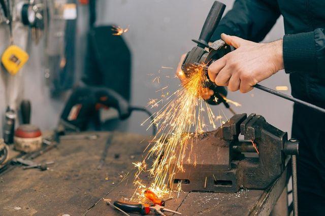 Metal lavoratore utilizzando smerigliatrice. messa a fuoco selettiva e profondità di campo