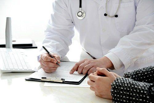 un dottore che scrive su una cartella clinica e una donna seduta accanto
