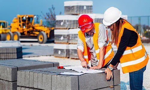 un uomo e una donna con delle pettorine arancioni e degli elmetti mentre guardano dei progetti appoggiati su dei mattoni grigi in un cantiere