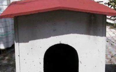 Casetta per il cane fatta di cemento con il tetto rosso