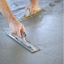 operaio che livella del cemento