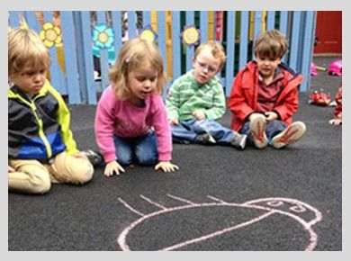 Children sitting around a pink chalk drawing of a large insect on the tarmac