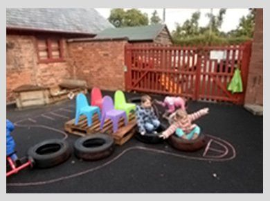 Children playing on tyres in an outdoor play area secured with a large wooden gate