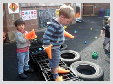 Little boys playing with traffic cones and tyres