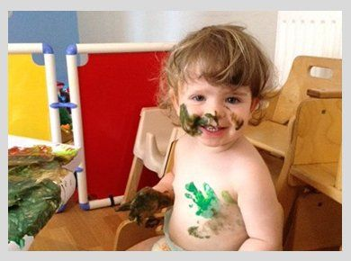 A smiling baby with tummy and face streaked with paint