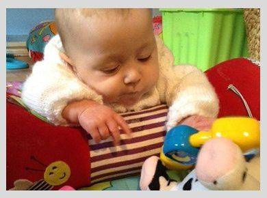 A tiny baby in a cuddly cardigan, looking at some plastic toys