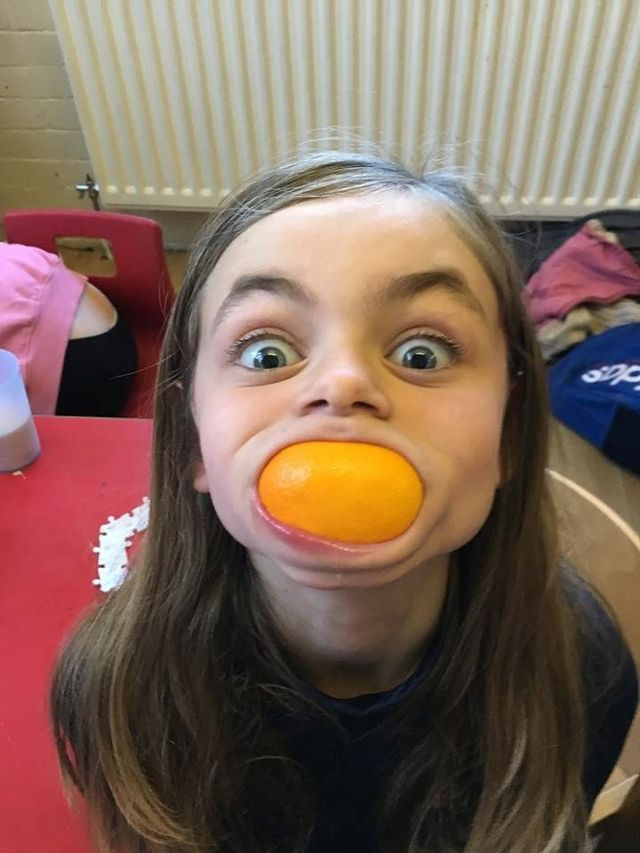 A little girl with a satsuma in her mouth
