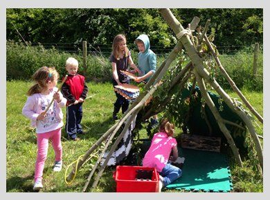 Children in a field constructing a tent from wood