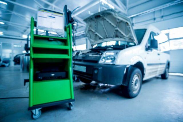 un carrello verde con sopra un monitor e sulla destra un furgone con il cofano aperto