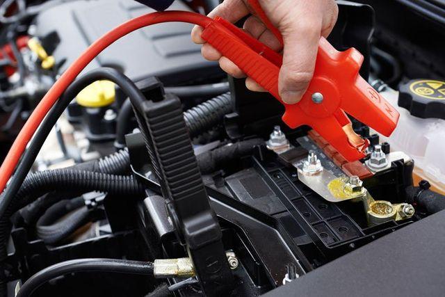 una mano con una pinza rossa di uno starter kit e vista del motore di una vettura