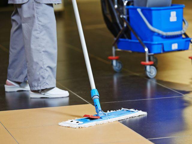 un inserviente che pulisce il pavimento con il mocio in microfibra