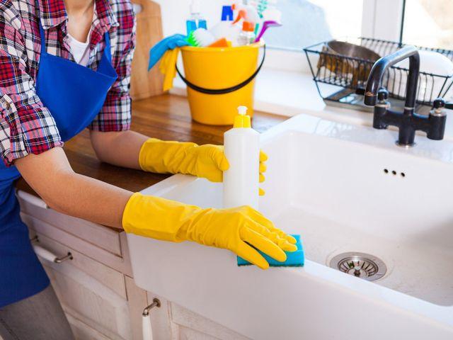 due mani con dei guanti gialli,una spugna e uno spruzzino