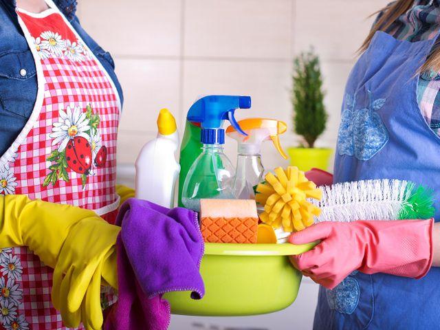 due inservienti che tengono un catino con dei prodotti da pulizia