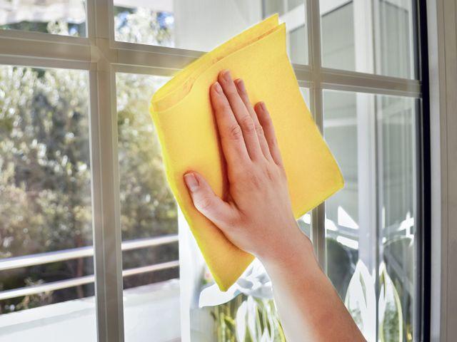 una mano che asciuga un vetro con un panno