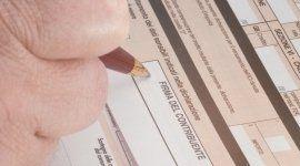 persona mentre firma su un documento nel campo FIRMA DEL CONTRIBUENTE