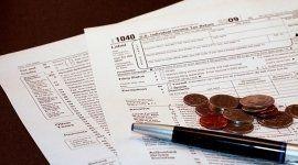 documenti monete e biro appoggiata sopra