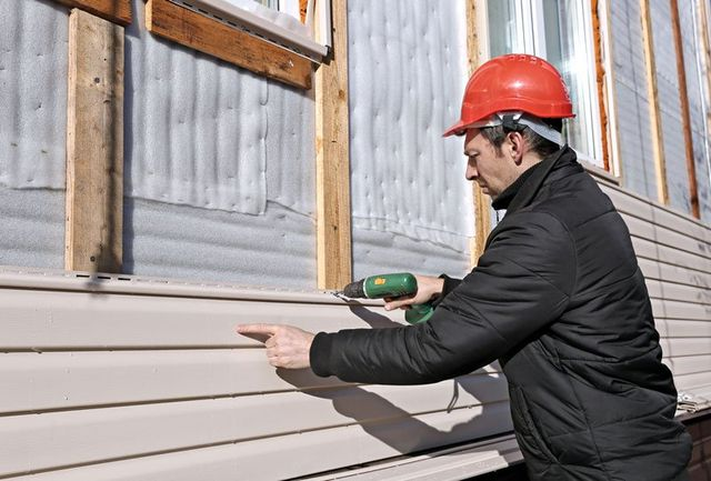 A worker installs panels beige siding on the facade of the house in CT