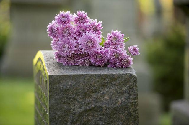una lapide in pietra con sopra dei fiori