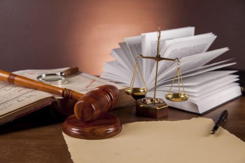 un martello di legno, una bilancia a due piatti e un libro di legge