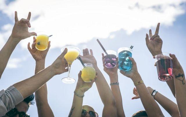delle mani con dei bicchieri con dei cocktail durante un brindisi