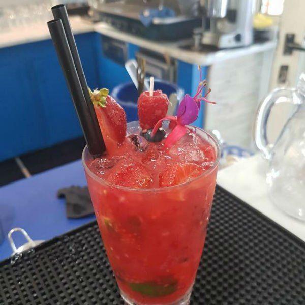 un cocktail rosso con ghiaccio, fragole e lamponi