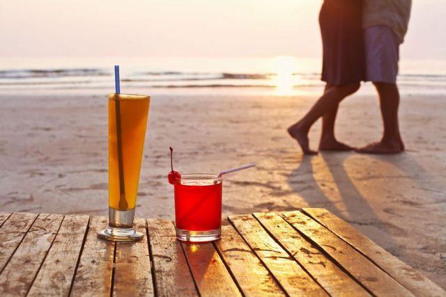 un bicchiere di un cocktail arancione e uno rosso su una passerella di legno con vista della spiaggia