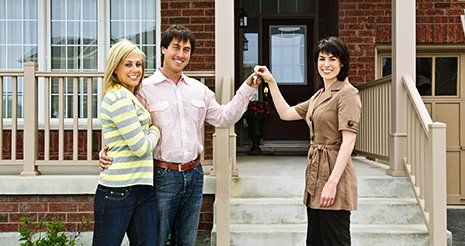 Realtor giving happy couple keys to their new home