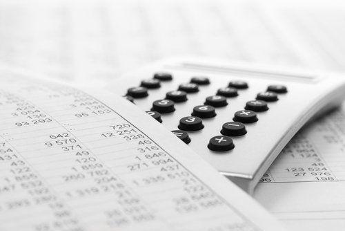 una calcolatrice e dei fogli contabili su un tavolo