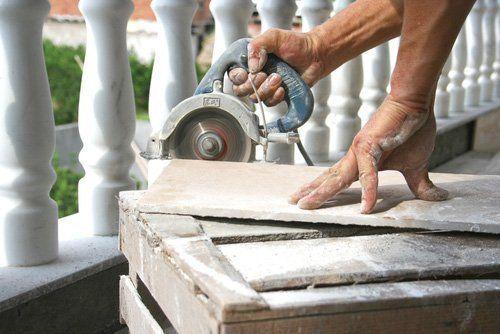 uomo tagliando piastrelle con frullino