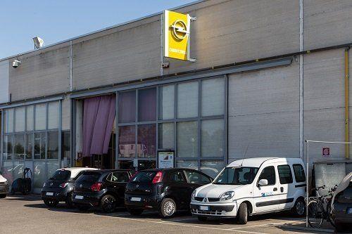 delle macchine parcheggiate fuori da una  carrozzeria e una bandiera della Opel