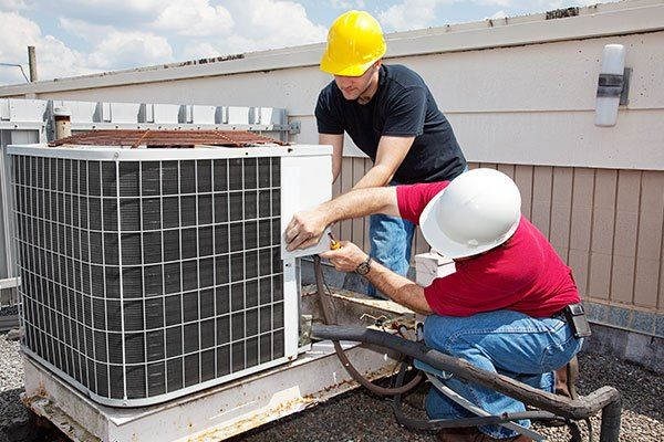 Men installing air conditioning system