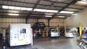 Inside of the garage with motor home and cars being worked on