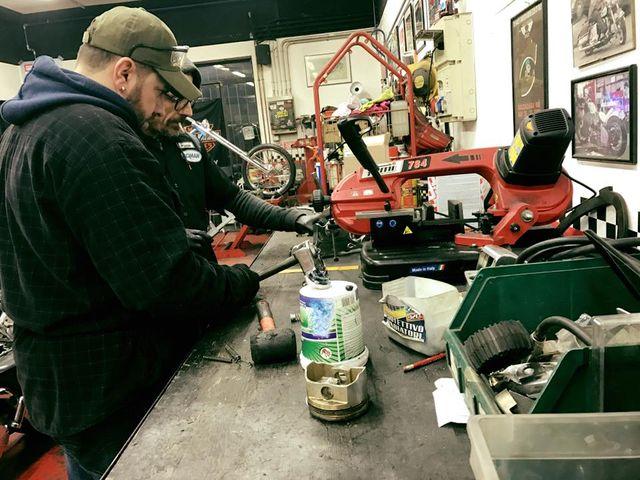 due meccanici al lavoro su un banco in officina